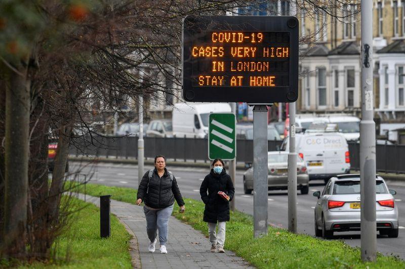 © Reuters. Alcuni passanti davanti a un cartello informativo sulla salute pubblica a Londra
