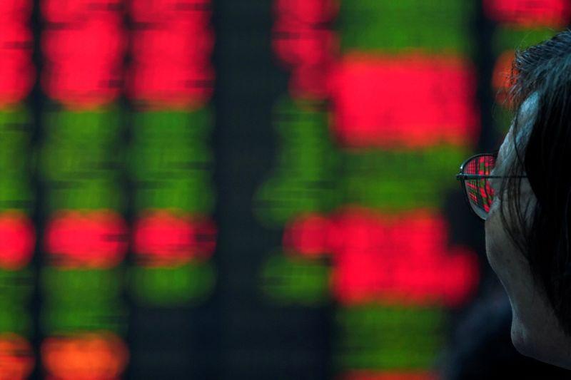 © Reuters. Un investitore osserva un tabellone con dati sugli indici della Borsa di Shanghai