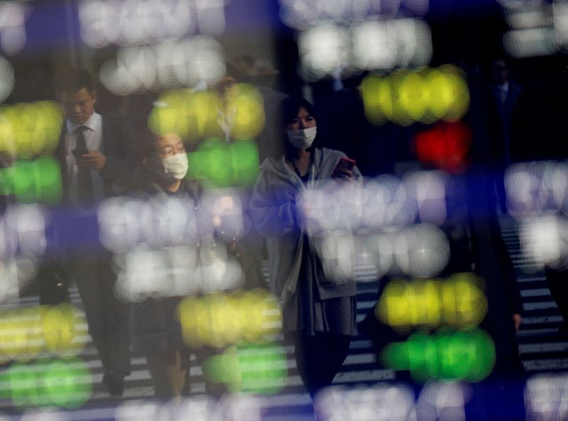 © Reuters. FILE PHOTO: Pedestrians wearing facial masks are reflected on an electric board showing stock prices outside a brokerage at a business district in Tokyo