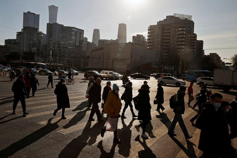 © Reuters. People cross a street during morning rush hour in front of the skyline of the CBD in Beijing