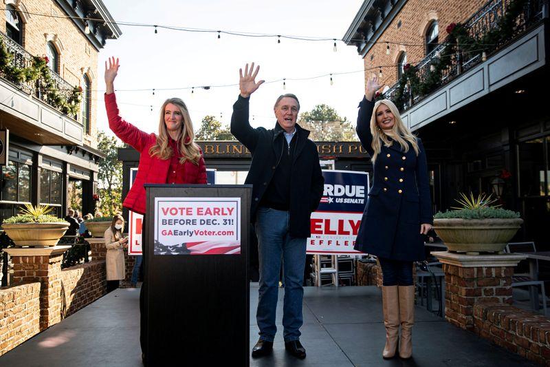 © Reuters. FILE PHOTO: Senator Kelly Loeffler (R-GA), Senator David Perdue (R-GA), and White House senior advisor Ivanka Trump wave during a campaign event in Milton