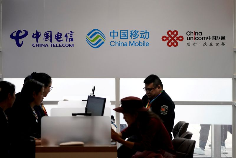 © Reuters. FILE PHOTO: Signs of China Telecom, China Mobile and China Unicom are seen during the China International Import Expo at the National Exhibition and Convention Center in Shanghai