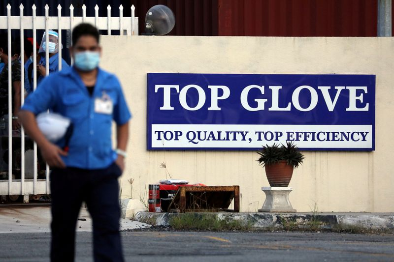 © Reuters. FILE PHOTO: A worker leaves a Top Glove factory after his shift in Klang