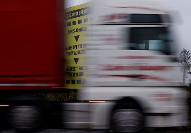 © Reuters. A lorry passes a Brexit themed poster on the road close to the border between Northern Ireland and Ireland near Newry