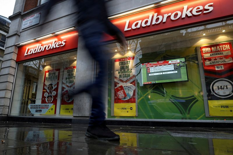 © Reuters. FILE PHOTO: A pedestrian walks past a branch of Ladbrokes in London