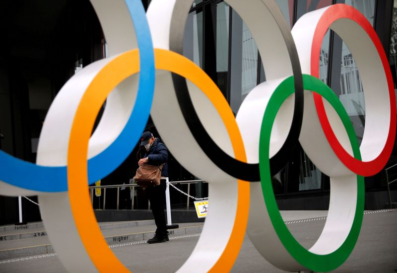 © Reuters. FILE PHOTO: Man is seen through the Olympic rings in Tokyo