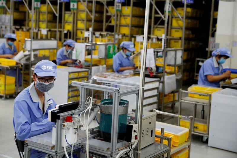 © Reuters. FILE PHOTO: Employees wearing face masks work at a factory of the component maker SMC during a government organised tour of its facility following the outbreak of the coronavirus disease (COVID-19), in Beijing