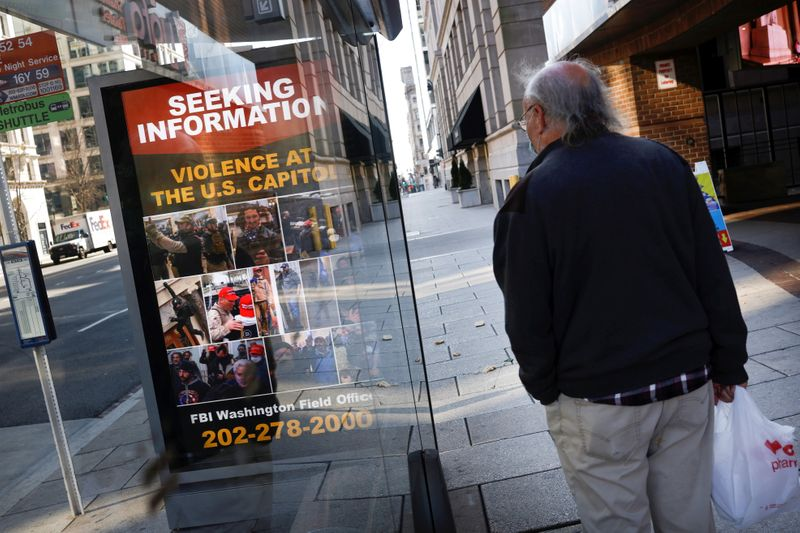 © Reuters. A local resident looks at a billboard with pictures of supporters of U.S. President Donald Trump wanted by the FBI who participated in storming the U.S. Capitol, forcing Congress to postpone a session certifying the results of the 2020 U.S. presidential el