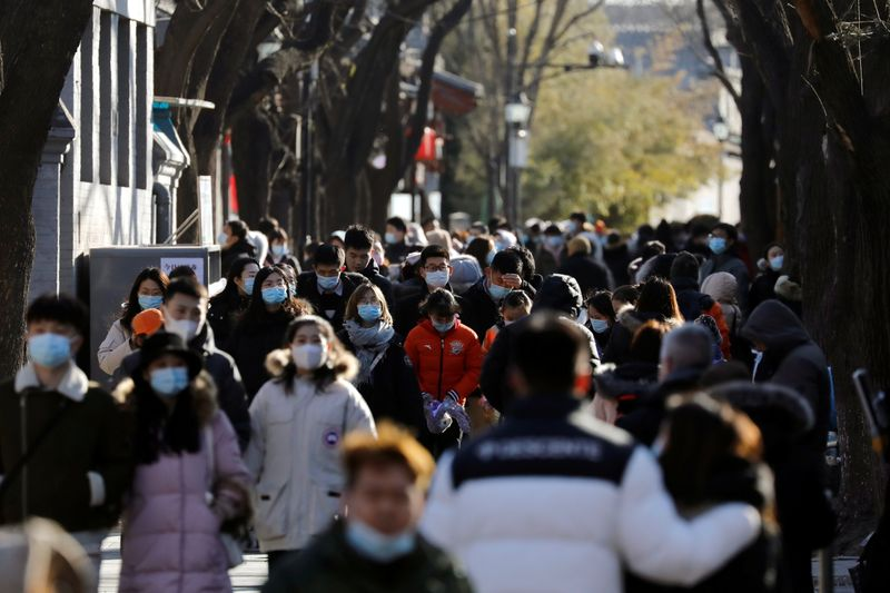 © Reuters. People wearing face masks following the coronavirus disease (COVID-19) outbreak walk along Nanluoguxiang alley