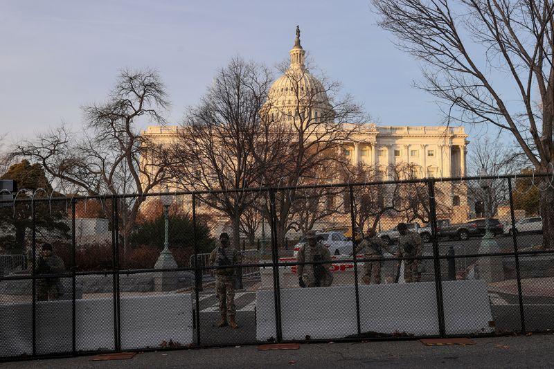 © Reuters. FILE PHOTO: Workers install razor wire atop the unscalable fence surrounding the U.S. Capitol in Washington