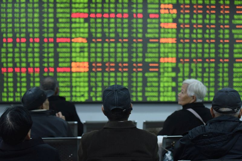 © Reuters. Investors sit in front of a board showing stock information at a brokerage house on the first day of trade in China since the Lunar New Year, in Hangzhou