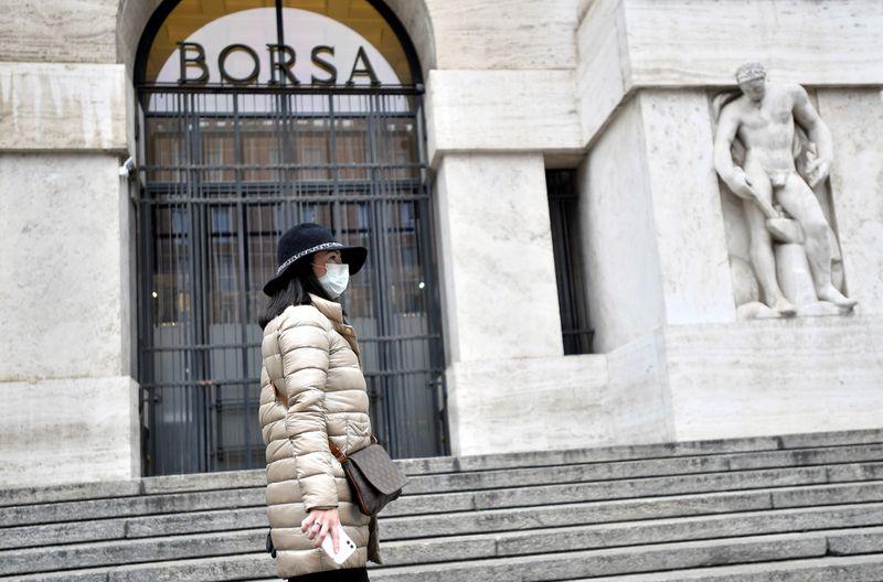 © Reuters. Una donna con una mascherina davanti all'ingresso della Borsa di Milano