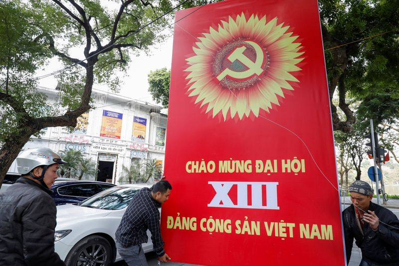 © Reuters. Workers set up a poster for upcoming 13th National Congress of the ruling Communist Party of Vietnam, on a street in Hanoi