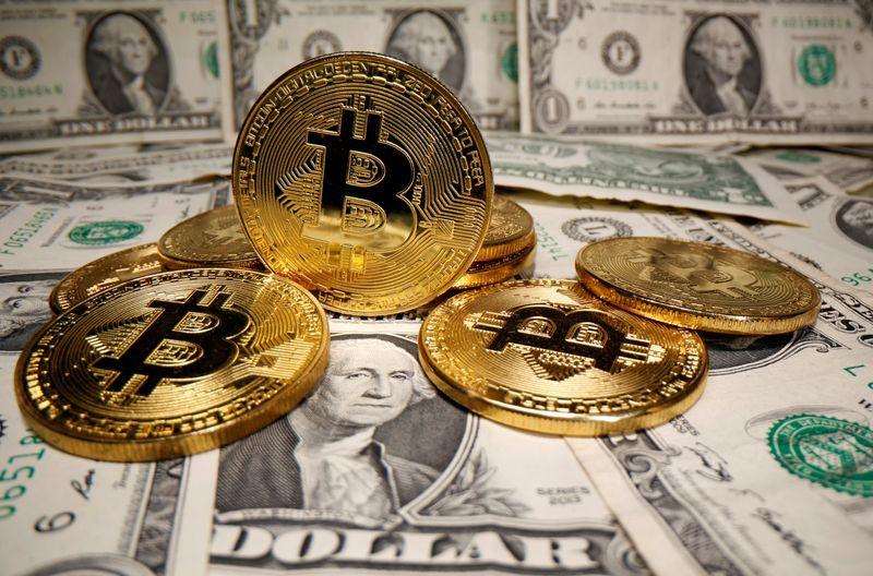 © Reuters. FILE PHOTO: Representations of virtual currency Bitcoin are placed on U.S. Dollar banknotes