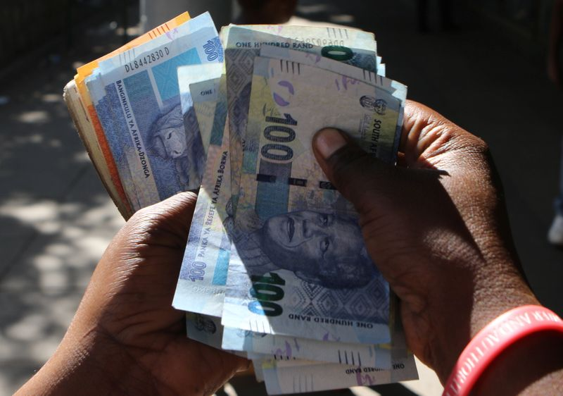 © Reuters. A street money changer counts South African Rands in Harare