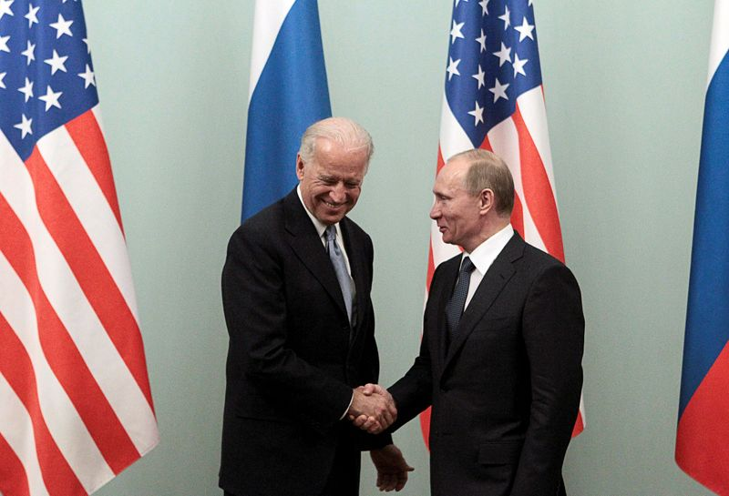 © Reuters. FILE PHOTO: Russian Prime Minister Putin shakes hands with U.S. Vice President Biden during their meeting in Moscow