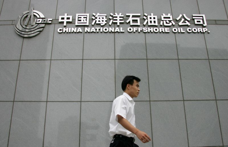 © Reuters. A man walks past the China National Offshore Oil Corp building in Beijing.
