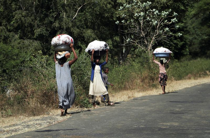 © Reuters. FILE PHOTO: Girls carry laundry in Soroka town in Amhara region near a border with Tigray