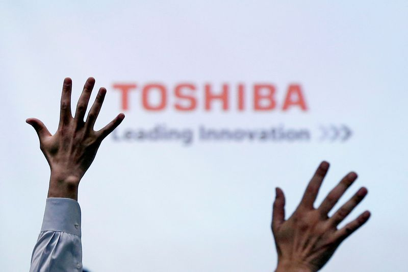 © Reuters. FILE PHOTO: Reporters raise their hands for a question during a Toshiba news conference at the company headquarters in Tokyo