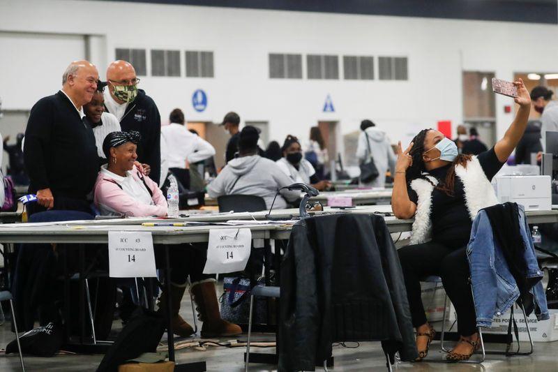 © Reuters.  FOTO DE ARCHIVO: Trabajadores electorales se hacen pasar por los votos que se siguen contando en el TCF Center el día después de las elecciones presidenciales de Estados Unidos de 2020 en Detroit, Michigan.