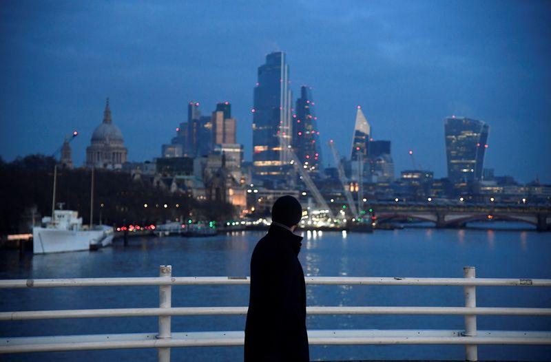 © Reuters. A man looks towards skyscrapers of the City of London financial district as he crosses Waterloo Bridge in London