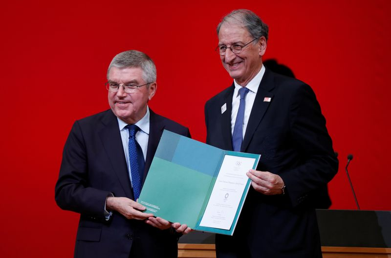 © Reuters. IOC President Bach presents invitation to Olympic Games to President of the French Olympic Committee Masseglia during a ceremony in Tokyo