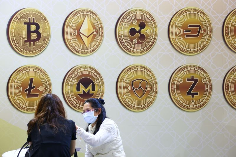© Reuters. Customers talk against a backboard with signs of cryptocurrency during 2020 Taipei International Finance Expo in Taipei,