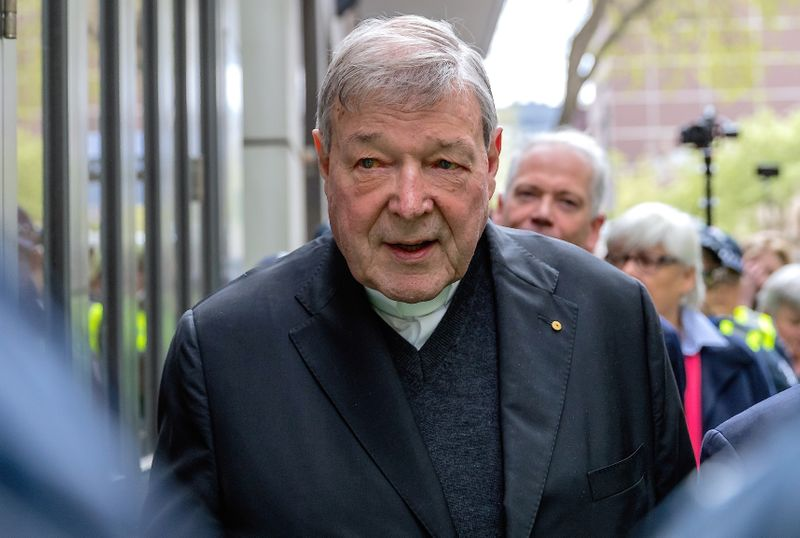© Reuters. FILE PHOTO - Vatican Treasurer Cardinal George Pell is surrounded by Australian police as he leaves the Melbourne Magistrates Court in Australia