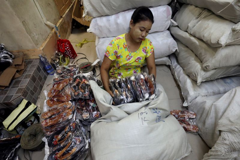 © Reuters. FILE PHOTO: A staff arranges footwears from a wholesale shop in Yangon