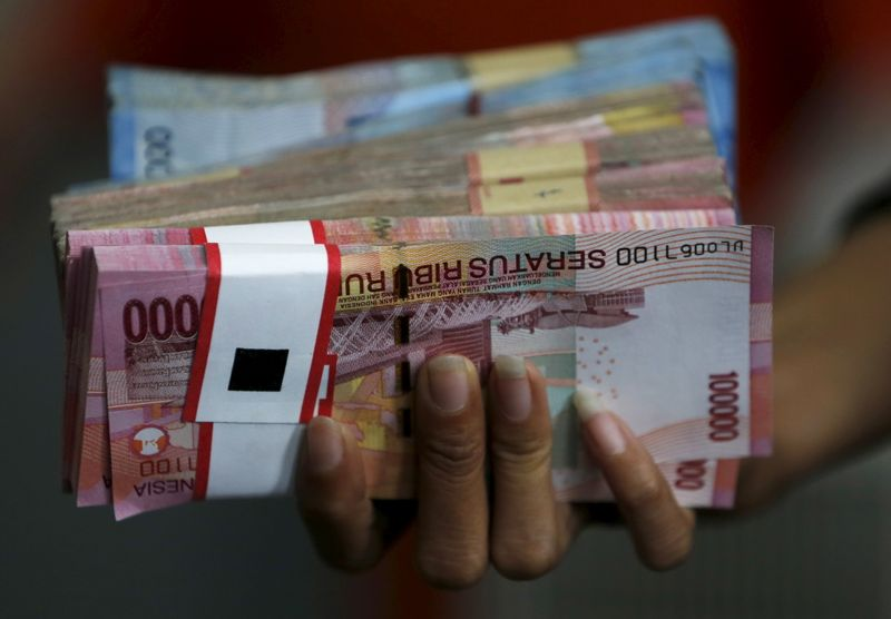 © Reuters. An employee of a money changer holds a stack of Indonesia rupiah notes before giving it to a customer in Jakarta