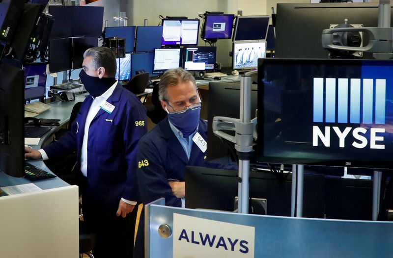 © Reuters. FILE PHOTO: Traders wearing masks work, on the first day of in person trading since the closure during the outbreak of the coronavirus disease (COVID-19) on the floor at the NYSE in New York