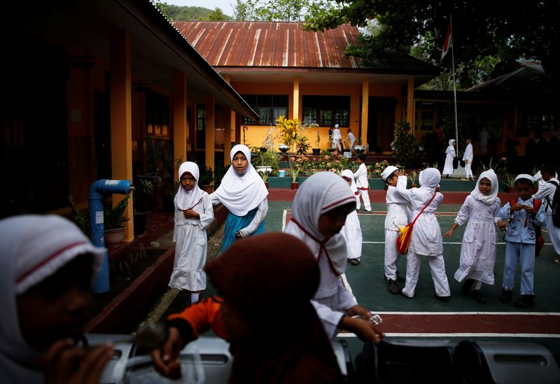 © Reuters. FILE PHOTO: Students gather in front of their classroom on the Maitara island, in Tidore, North Maluku province