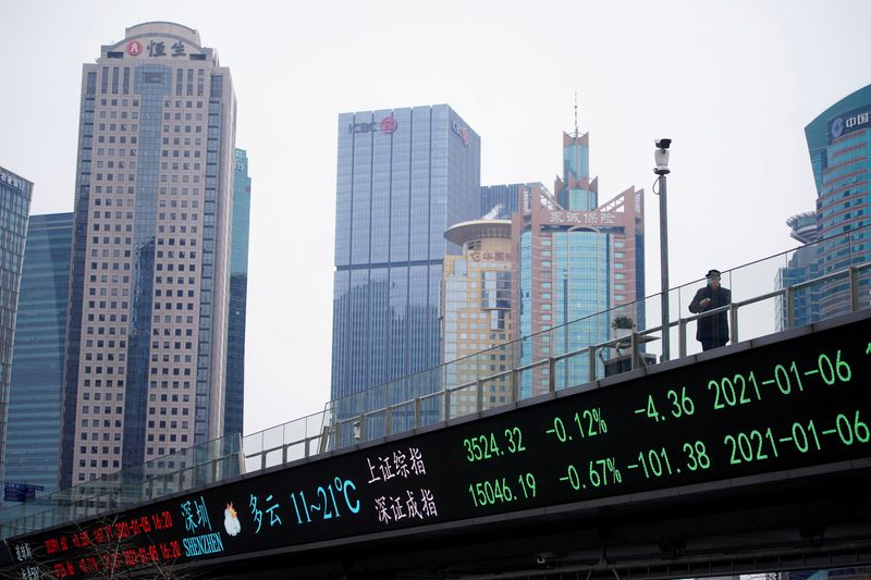 © Reuters. FILE PHOTO: A man stands on an overpass with an electronic board showing Shanghai and Shenzhen stock indexes in Shanghai