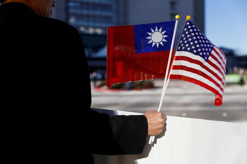 © Reuters. FILE PHOTO: A demonstrator holds flags of Taiwan and the United States in support of Taiwanese President Tsai Ing-wen during an stop-over after her visit to Latin America in Burlingame