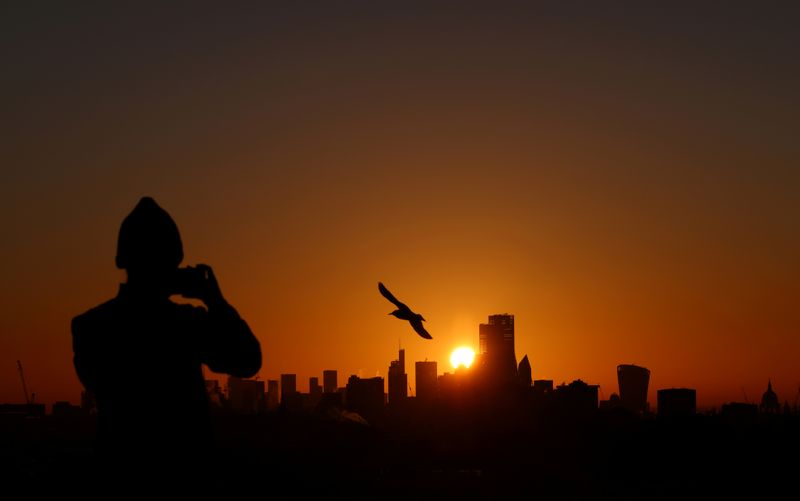 © Reuters. FILE PHOTO: A person takes a photograph of the London skyline from Primrose Hill