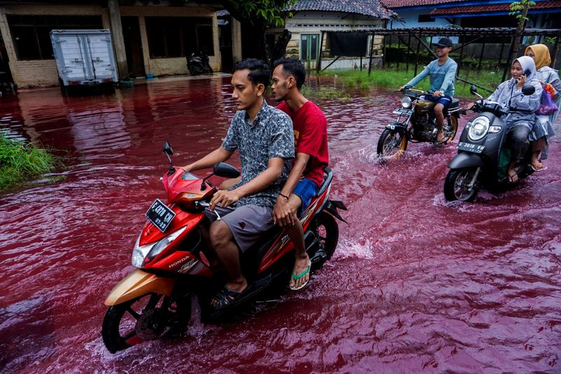 © Reuters. People ride motorbikes through a flooded road in Pekalongan