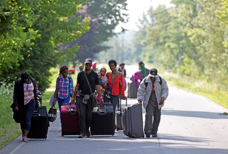 © Reuters. FILE PHOTO: Three families that claimed to be from Burundi walk down Roxham Road to cross into Quebec at the US-Canada border in Champlain, New York