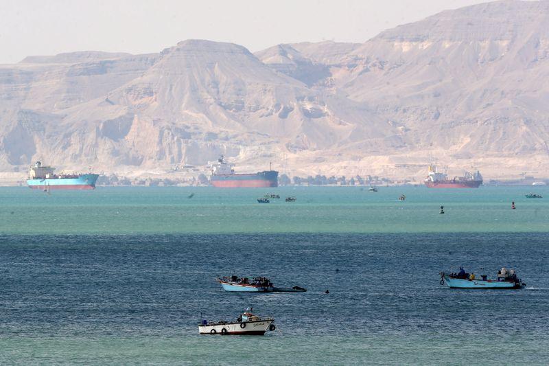 Tugs, dredgers still struggle to free ship blocking Suez Canal