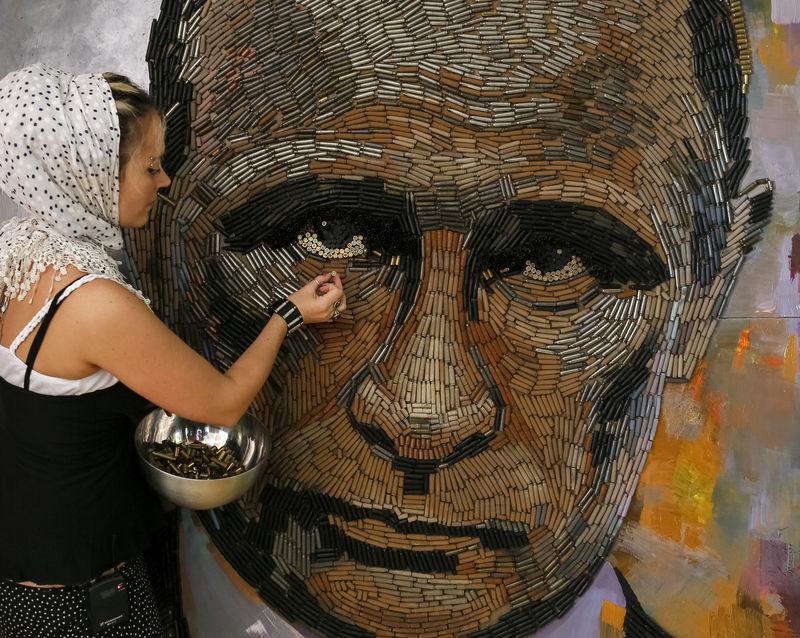 © Reuters. Украинская художница Дарья Марченко у сделанного ею из гильз, собранных на востоке Украины, портрета Владимира Путина