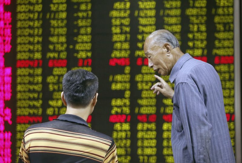 © Reuters. Investors talk in front of an electronic board showing stock information at a brokerage house in Beijing