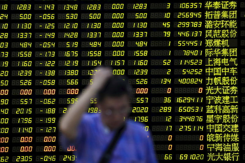 © Reuters. An investor stands in front of electronic board showing stock information at brokerage house in Shanghai