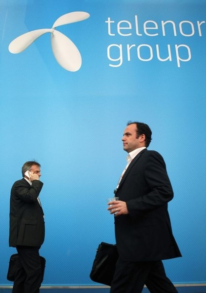 © Reuters. Visitors walk past a Telenor Group stand at the Mobile World Congress in Barcelona