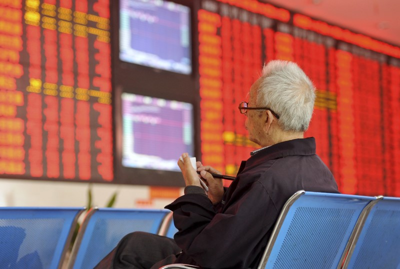 © Reuters. An investor writes on papers as he sits in front of an electronic board showing stock information at a brokerage house in Fuyang