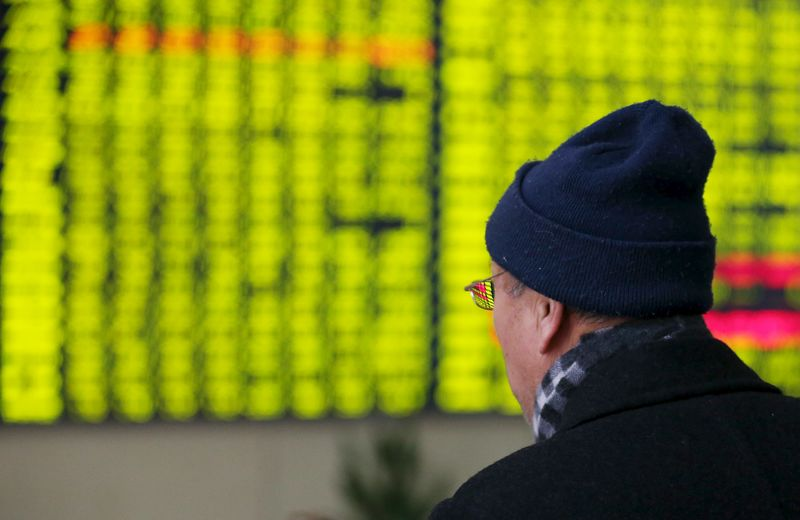 © Reuters. Investor looks at an electronic screen showing stock information at brokerage house in Nantong