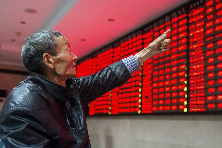 © Reuters. An investor points to an electronic board showing stock information as he speaks to another investor, at a brokerage house in Nanjing, Jiangsu province, China