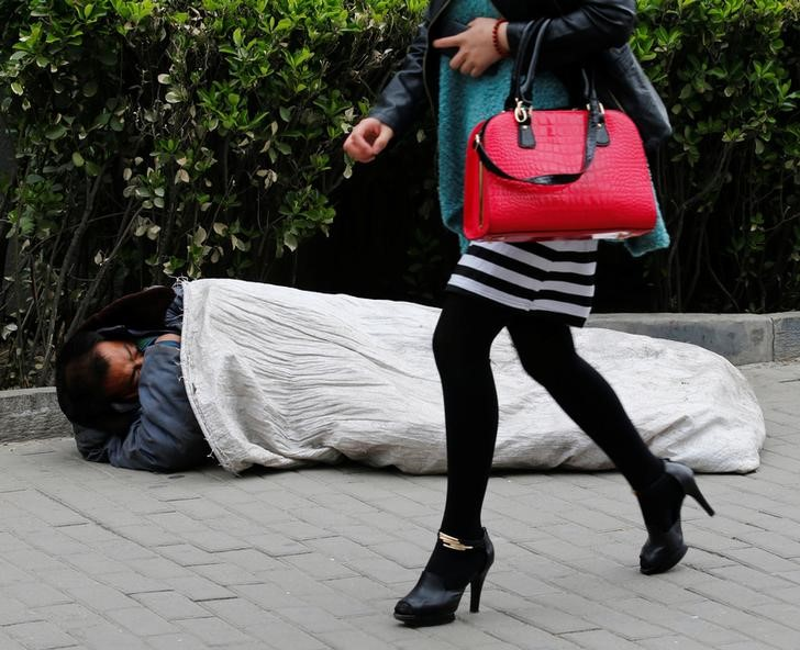 © Reuters. A woman walks past a homeless man sleeping on the street in Beijing