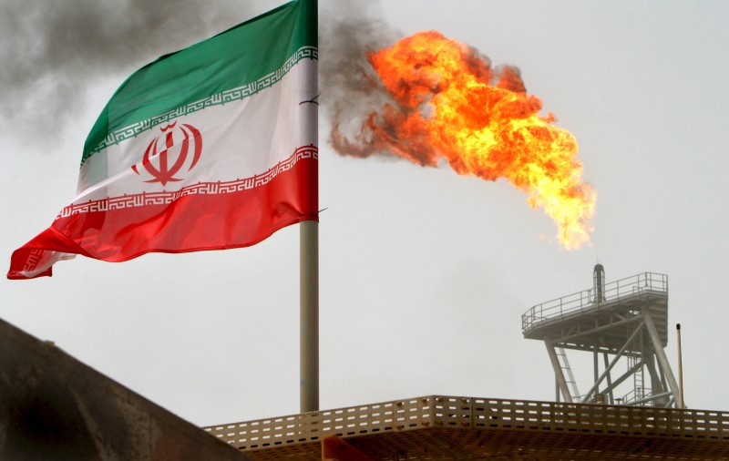 © Reuters. A gas flare on an oil production platform in the Soroush oil fields is seen alongside an Iranian flag in the Gulf