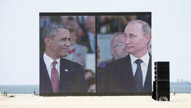 © Reuters. Президент США Барак Обама (слева) и президент России Владимир Путин  на экране в Уистреаме, Франция