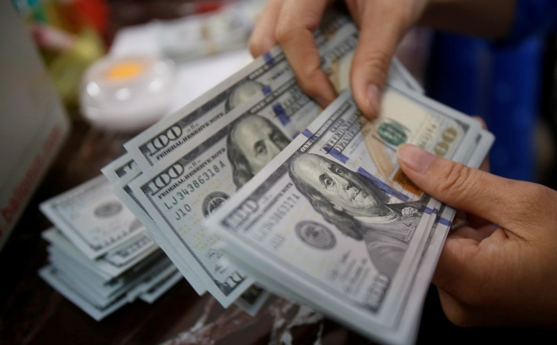 © Reuters. Банковский сотрудник пересчитывает доллары США в Ханое
