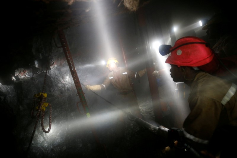 © Reuters. FILE PHOTO: Mine workers employed at Sibanye Gold's Masimthembe shaft operate a drill in Westonaria